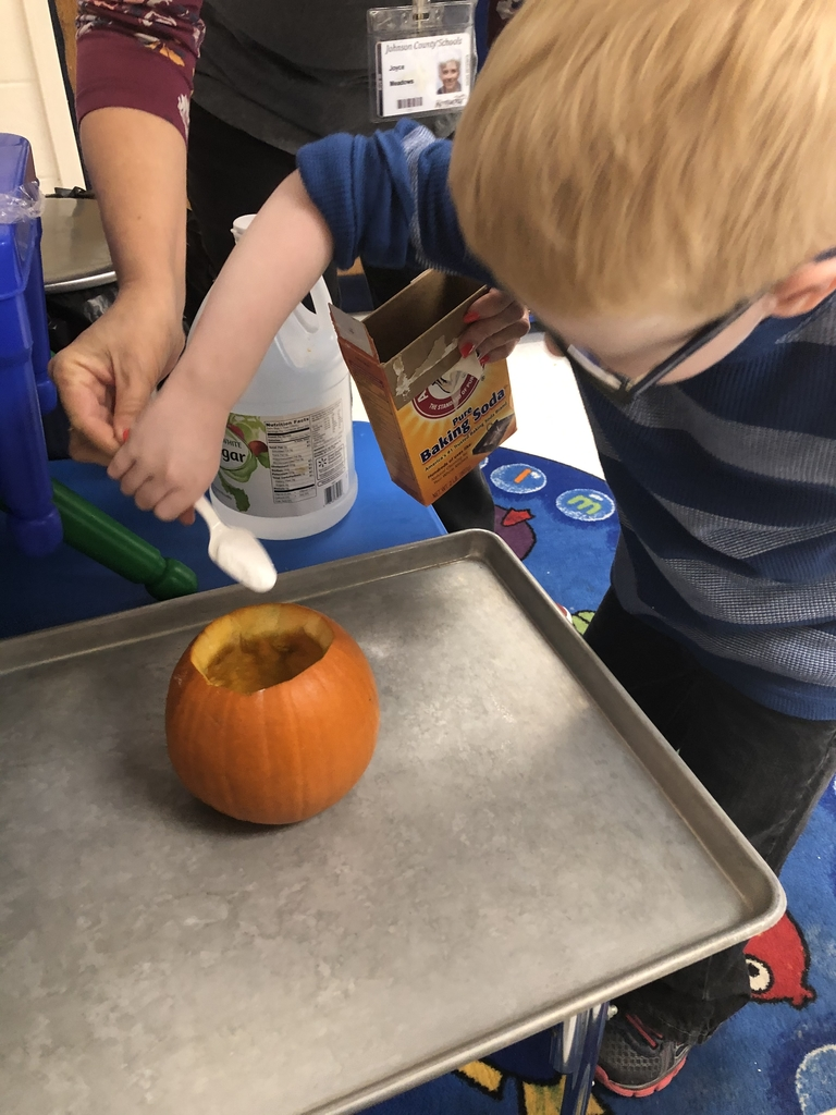 Elijah placing baking soda in the pumpkin!