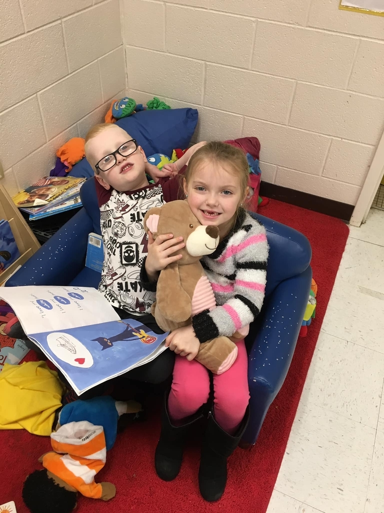 Elijah reading and sharing a story with Emily and her friend bear!